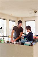 Father and young son clearing up in kitchen Stock Photo - Premium Royalty-Freenull, Code: 649-07585463