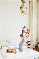 Young sisters playing with soft toy on the bed Stock Photo - Premium Royalty-Freenull, Code: 649-07585468