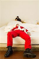 Young boy dressed up as santa claus lying on bed Stock Photo - Premium Royalty-Freenull, Code: 649-07585486