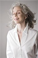 Mature woman smiling, eyes closed Stock Photo - Premium Royalty-Freenull, Code: 614-07587618