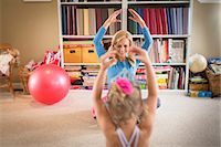 Mother and young daughter practicing ballet in sitting room Stock Photo - Premium Royalty-Freenull, Code: 614-07587666