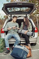 Man pouring coffee for woman while sitting at car trunk during camping Stock Photo - Premium Royalty-Freenull, Code: 698-07587729