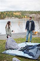 Couple communicating while setting up tent on lakeshore Stock Photo - Premium Royalty-Freenull, Code: 698-07587761