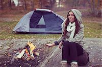 Portrait of woman cooking sausage in campfire against tent in forest Stock Photo - Premium Royalty-Freenull, Code: 698-07587771