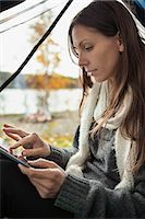 Young woman using digital tablet in tent Stock Photo - Premium Royalty-Freenull, Code: 698-07587779