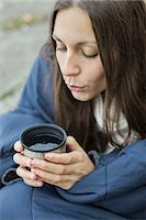 Woman wrapped in blanket blowing on coffee Stoc