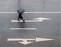 people with umbrellas in the rain - High angle view of woman with umbrella walking on road Stock Photo - Premium Royalty-Freenull, Code: 698-07587795