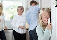 Portrait of smiling girl holding door handle with family in background at kitchen Stock Photo - Premium Royalty-Freenull, Code: 698-07587831