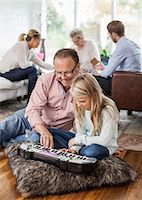 Grandfather and granddaughter playing piano with family in background at home Stock Photo - Premium Royalty-Freenull, Code: 698-07587867