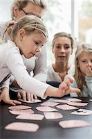 selecting - Girl playing card puzzle game with family at home Stock Photo - Premium Royalty-Freenull, Code: 698-07587871