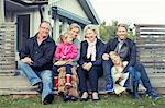 Portrait of happy multi-generation family sitting together in yard