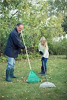 grandfather and granddaughter raking autumn leaves at yard Stock Photo - Premium Royalty-Freenull, Code: 698-07587880