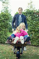 stockholm - Playful father pushing daughters on wheelbarrow at yard Stock Photo - Premium Royalty-Freenull, Code: 698-07587881
