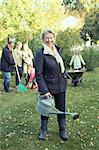 Portrait of senior woman carrying watering can while gardening with family at yard