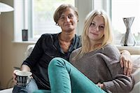 Portrait of mother and daughter sitting in living room Stock Photo - Premium Royalty-Freenull, Code: 698-07587889