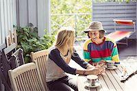 Grandmother and granddaughter having coffee in yard Stock Photo - Premium Royalty-Freenull, Code: 698-07587915