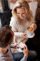 High angle view of young couple having coffee at cafe Stock Photo - Premium Royalty-Freenull, Code: 698-07587933
