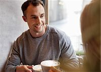Young man having coffee with woman at cafe Stock Photo - Premium Royalty-Freenull, Code: 698-07587934
