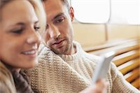 Couple using mobile phone together on ferry Stock Photo - Premium Royalty-Freenull, Code: 698-07587948