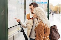 Young couple reading time table on bus stop Stock Photo - Premium Royalty-Free, Artist: Ikon Images, Code: 698-07587969