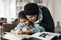 Mother embracing daughter studying at home Stock Photo - Premium Royalty-Freenull, Code: 698-07588001