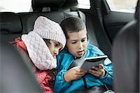 Siblings using digital tablet in car Stock Photo - Premium Royalty-Freenull, Code: 698-07588023