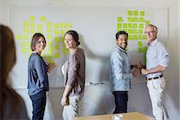 Happy business people standing by whiteboard at office Stock Photo - Premium Royalty-Freenull, Code: 698-07588044