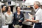 Team of inspectors talking to chef in commercial kitchen