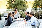 Group of business people working at table on patio