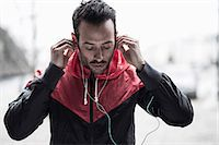Sporty man in jacket adjusting headphones Stock Photo - Premium Royalty-Freenull, Code: 698-07588106