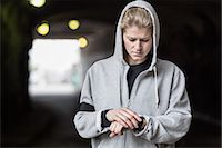 stop watch - Female jogger checking time in tunnel Stock Photo - Premium Royalty-Freenull, Code: 698-07588109