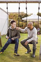 swing (sports) - Father and son sitting on swings in garden Stock Photo - Premium Royalty-Freenull, Code: 698-07588163