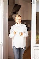 Happy mature woman with coffee cup leaving house Stock Photo - Premium Royalty-Freenull, Code: 698-07588166