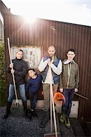 Portrait of confident family with gardening equipment standing against house Stock Photo - Premium Royalty-Freenull, Code: 698-07588181