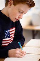 High school boy writing at desk in classroom Stock Photo - Premium Royalty-Freenull, Code: 698-07588241