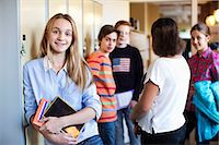 Portrait of school girl standing at locker room with friends in background Stock Photo - Premium Royalty-Freenull, Code: 698-07588298