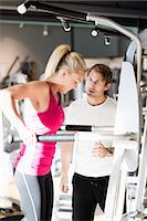 Instructor motivating customer exercising at gym Stock Photo - Premium Royalty-Freenull, Code: 698-07588307