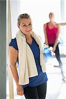 Portrait of fit senior woman with towel and water bottle standing at gym Stock Photo - Premium Royalty-Freenull, Code: 698-07588321