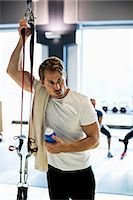 Tired man with towel and water bottle at health club Stock Photo - Premium Royalty-Freenull, Code: 698-07588323