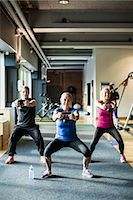 Full length of friends lifting kettlebells at health club Stock Photo - Premium Royalty-Freenull, Code: 698-07588328