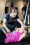 Male instructor assisting senior woman in doing sit-ups at gym