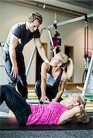 Instructors with senior woman doing sit-ups at health club Stock Photo - Premium Royalty-Freenull, Code: 698-07588332