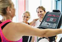 Friends looking at woman exercising on treadmill at gym Stock Photo - Premium Royalty-Freenull, Code: 698-07588343