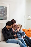 Lesbian couple with girl in living room Stock Photo - Premium Royalty-Freenull, Code: 698-07588532
