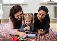 Smiling lesbian couple and girl using digital tablet at home Stock Photo - Premium Royalty-Freenull, Code: 698-07588536