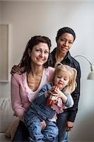 Portrait of lesbian couple with girl at home Stock Photo - Premium Royalty-Freenull, Code: 698-07588540