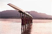 sport rowing teamwork - Rowing team carrying row boat overhead in still lake Stock Photo - Premium Royalty-Freenull, Code: 6113-07588633