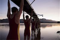sport rowing teamwork - Rowing team carrying boat overhead into lake Stock Photo - Premium Royalty-Freenull, Code: 6113-07588640