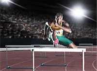 Runner clearing hurdle on track Stock Photo - Premium Royalty-Freenull, Code: 6113-07588677