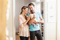 popping (bursting not corks or pimples) - Mid adult coupe playing with baby girl at doorway Stock Photo - Premium Royalty-Freenull, Code: 698-07588602